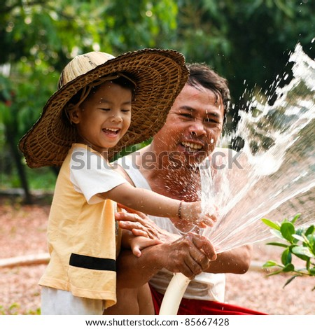 grandson and grandfather watering flower