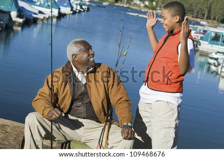 Grandson explaining something to grandfather through hand gesture