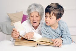 Grandson is looking at photo album together with his grandmother