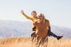 Grandson piggyback with his grandfather in autumn.