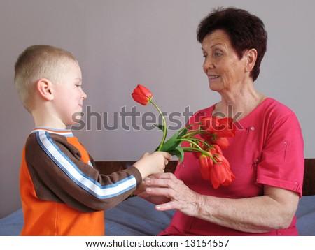 grandson present flowers to grandmother