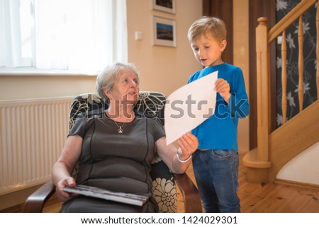 Grandson shows grandmother  picture with painted picture by himself