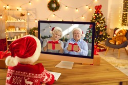 Grandson video calling grandma and grandpa in lockdown on Xmas holidays. Little grandchild sitting at computer screen, talking to happy grandparents who are showing Christmas presents they prepared