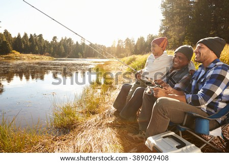 Grandson With Father And Grandfather Fishing By Lake
