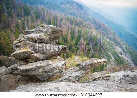 Granit boulder on Moro Rock hiking track in Sequoia National Park, California, USA. Scenic view to Sequoia and Kings Canyon NP giant forests and foggy valleys landscape of Sierra Nevada mountain range #1310944397