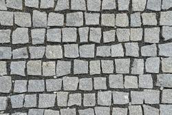 Granite cobblestone and small gravel pavement background. Full frame of irregular cobble. Natural stone textured background