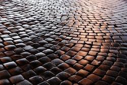 Granite cobblestones of the Belgian block pavement are photographed at night.