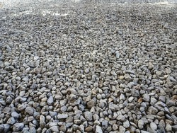 Granite gravel of macadam, rock gray crushed for construction on the ground. Scree texture background. Gravel is a loose aggregation of rock fragments.