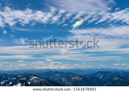 Granite mountain hike in Washington state. View from the peak of the lookout building. mountain range with multiple peaks visible under the bright blue sky and a rainbow cloud