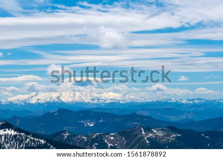 Granite mountain hike in Washington state. View from the peak of the lookout building. mountain range with multiple peaks visible under the bright blue sky