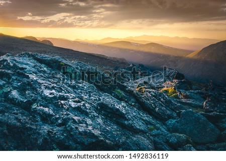 Granite outcrop overlooking sunbeams through the mountains at sunset #1492836119