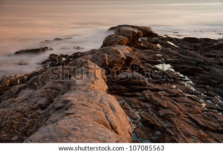 Granite rocks atop million year old igneous volcanic rock at sunset during low tide on the maine coast showing the erosion of the rock due to waves and tides