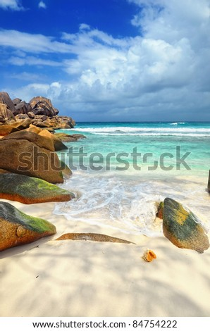 Granite rocky beaches on Seychelles islands, La Digue. Big orange shell in the surf