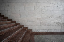 Granite stairs on the background of a wall of shell rock side view