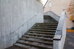 Granite stairs with foliage and a concrete wall at autumn day.