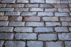 granite stone wet pavement, old stone paving, rough hewn skier on an old street, historic paving