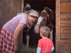 Granma is teaching grandson to do chores, keep the house, hold the bridle Horses at the stable are waiting for oat. Summer holidays at the village