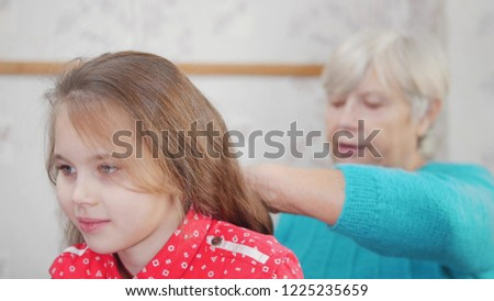 Granny enjoys combing hair to baby on sunny morning. Good time at home. #1225235659