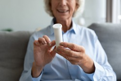 Granny sit on couch, close up focus on older female hands holds package with B complex supplements, read instruction daily multivitamin for seniors Vitamin B12, heart disease prevention pills concept