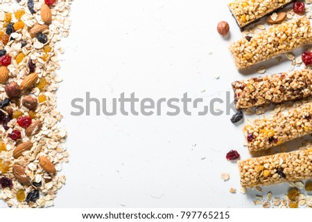 Granola bar and ingredients. Healthy sweet dessert snack. Cereal granola bar with nuts, fruit and berries on a white stone table. Top view copy space.