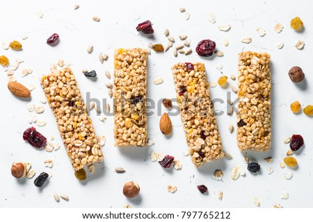 Granola bar. Healthy sweet dessert snack. Cereal granola bar with nuts, fruit and berries on a white stone table. Top view.