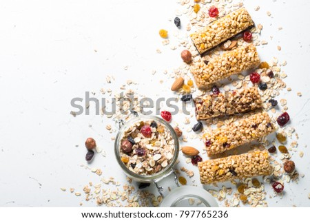 Granola bar. Healthy sweet dessert snack. Cereal granola bar with nuts, fruit and berries on a white stone table. Top view copy space.