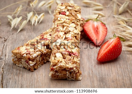 Granola bar with strawberries on wooden background