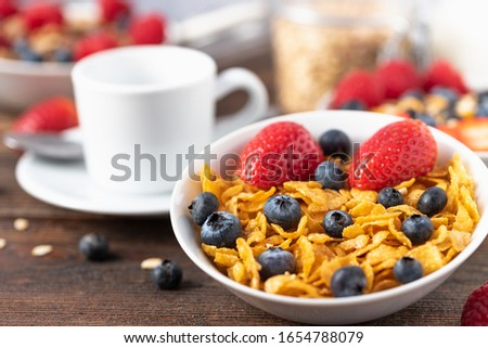 Granola chips with blueberries and raspberries in white bowl in dark wooden desk.