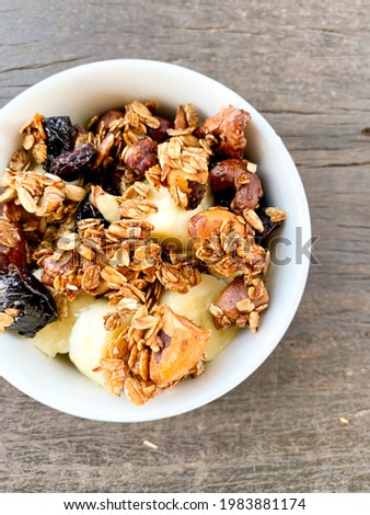 Granola is a breakfast cereal usually consisting of oats, wheatgerm, sesame seeds, and dried fruit or nuts. Stock photo ©