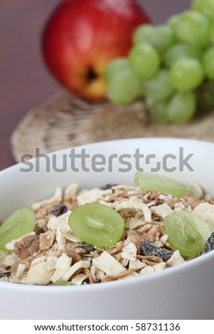 Granola with dried fruits garnished with fresh grapes - stock photo