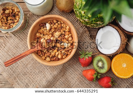 Granola with Greek yoghurt and fruit on a wooden background in a rustic style #644335291