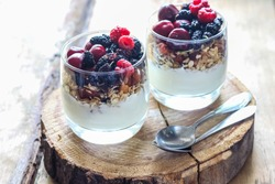 Granola with yogurt and berries in a glass. Delicious healthy American food for breakfast. Traditional US snack. Selective focus