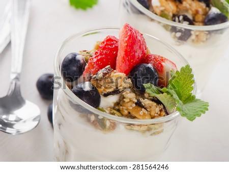 Granola with yogurt and berries in glasses. Selective focus