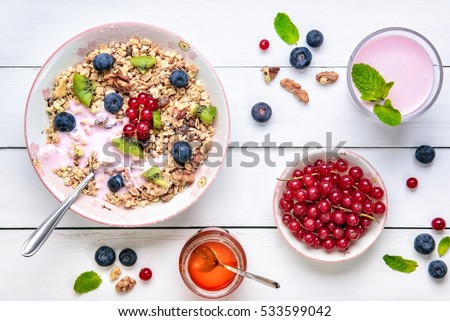 Granola with yogurt, fresh berries and honey for breakfast on a white wooden background. Top view.