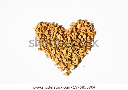 Granulated instant coffee in a shape of heart on a white background , love background,photo