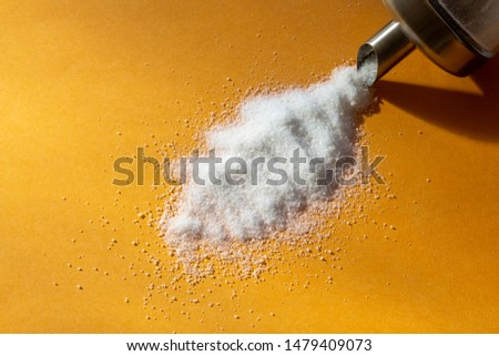 Granulated sugar on a yellow background.