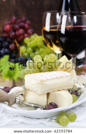 Grape and cheese with a bottle and glasses of red and white wine