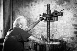 Grape harvest: old winemaker farmer working on a vintage wine press. Black and white picture
