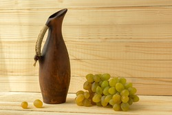 Grape jug on a wooden natural background. Rustic retro style. Antique clay jug with wine. Green juicy ripe grapes of the autumn harvest. the concept of agriculture, winemaking. Horizontal still life