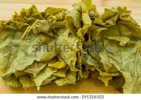 Grape leaves, vine leaves on a wooden chopping board