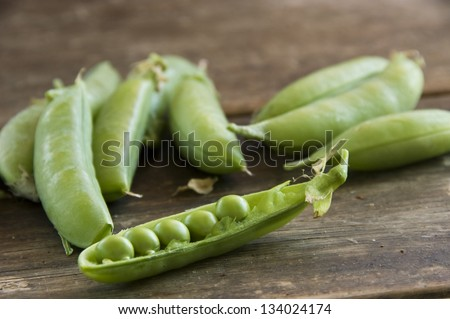 Grape of fresh shelled peas on a wooden table