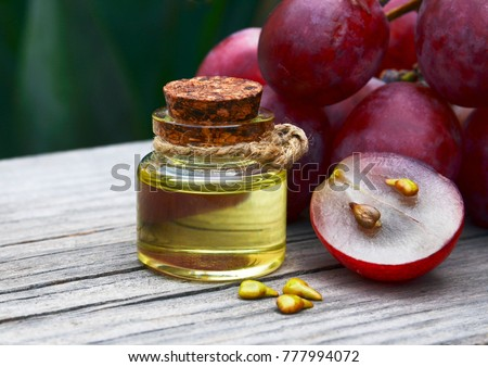 Grape seed oil in a glass jar and fresh grapes on old wooden table for spa and bodycare.Spa,Bio,Eco products concept. #777994072