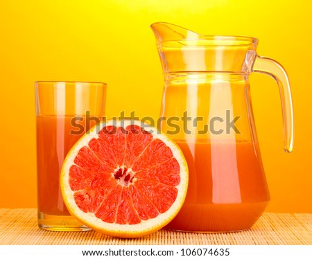 Grapefruit juice and grapefruit on bamboo mat on yellow background