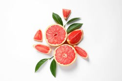 Grapefruits and leaves on white background, top view. Citrus fruits