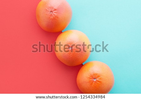 Grapefruits on Living Coral & pastel blue color diagonal background. Minimal summer concept flat lay. Year 2019 #1254334984