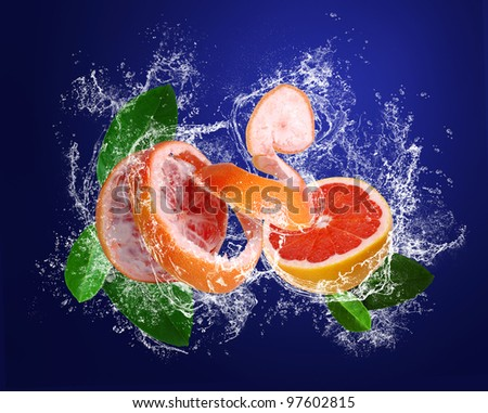 Grapefruits with leaves in water splashes in water splashes on the dark blue background