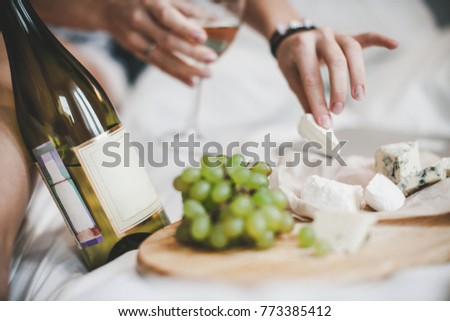 Grapes and bottle of white wine with cheese plate for the lunch in bedroom. Young woman is  eating brie and dor blue