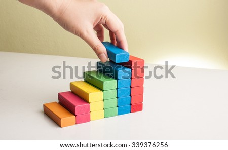 graph from block wood with hand and money concept #339376256