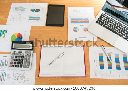 Graph sheet database with accounting document showing financial startup business planning with computer,calculator,notebook and pen on table at office,Work place,Financial planning making stats.