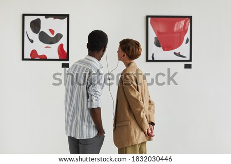 Graphic back view portrait of two young people looking at paintings and sharing audio guide while exploring modern art gallery exhibition, copy space Photo stock ©